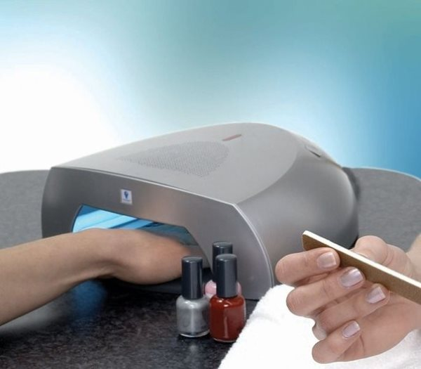 Девушка сушит ногти в УФ лампе.