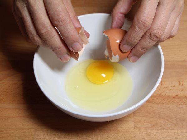 Девушка вбивает яйцо в миску.