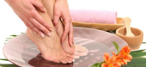 Девушка моет ноги в ванночке.