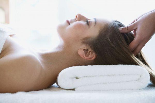 Девушке в салоне делают массаж головы.