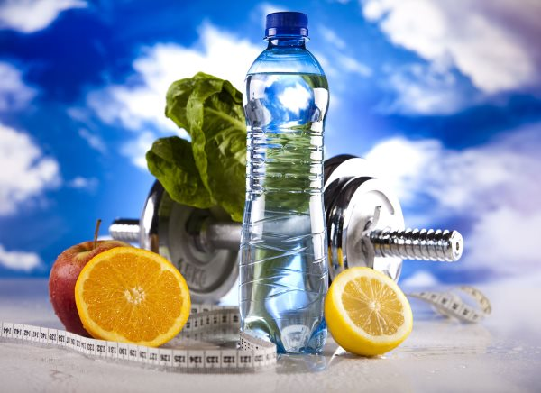 Бутылка воды, гантеля, сантиметр и фрукты.