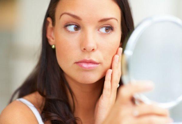 Девушка осматривает свое лицо в зеркало.