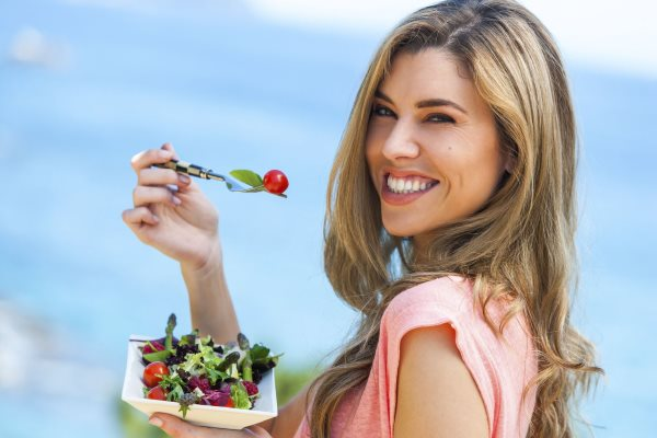 Девушка ест легкий салат.