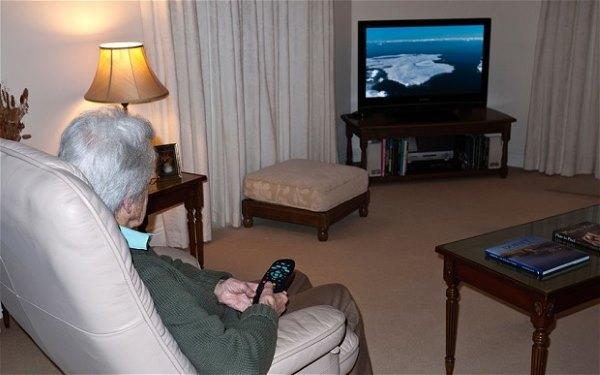 Пожилой мужчина смотрит телевизор